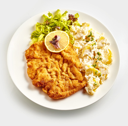 Above view of schnitzel with side dish, lemon and lettuce on white plate close-up over white background Stock Photo