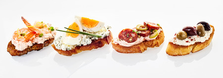 shrimp cocktail: Selection of fresh canapes in a header or banner format with assorted toppings including prawn, egg and chive, chorizo sausage and olives with red pepper on quark cheese on white with reflections