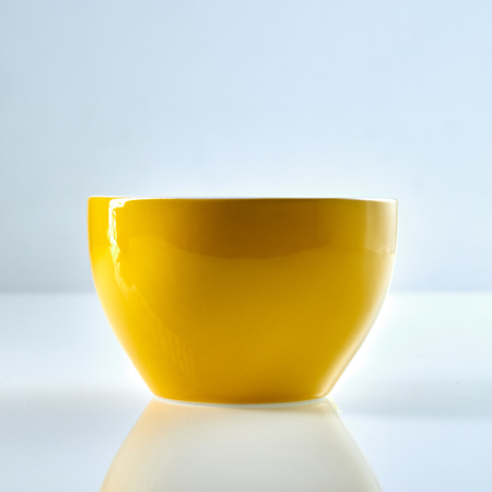High-sided plain yellow bowl of glossy ceramics from its side over glass surface with reflection, against white background Stock Photo