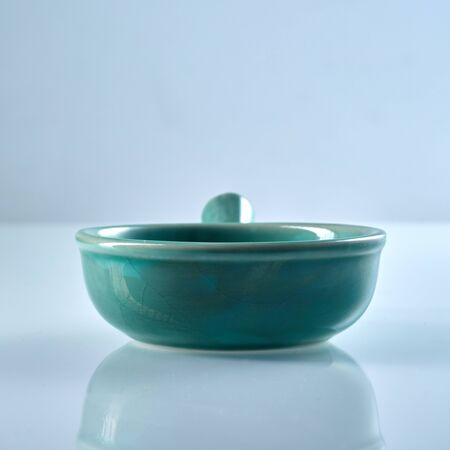 Green glazed ceramic ramekin with handle isolated on grey with copy space and reflection in a low angle view Stock Photo