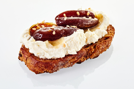 Date and sesame canape on quark cheese on a slice of toasted bread isolated on white with reflection for advertising