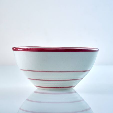 Simple white ceramic bowl with red stripes and rim for serving food over a grey background with reflection viewed from the side Stock Photo