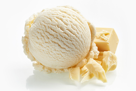 Speciality white milk chocolate ice cream in a single scoop with pieces of of a candy bar alongside as an ingredient isolated on white