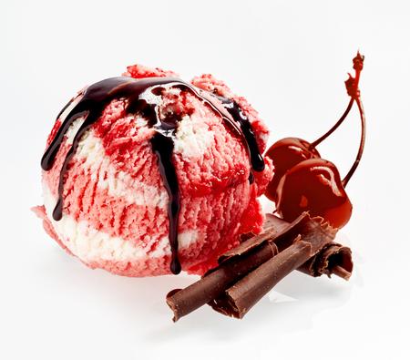 Gastronomisch kers en vanille-ijs-dessert besprenkeld met chocoladesaus en -schilfers met twee rijpe weelderige kersen ernaast