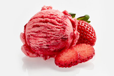 Tasty creamy strawberry ice cream with fresh ripe red succulent fruit alongside for advertising or a menu in a parlor or restaurant Фото со стока