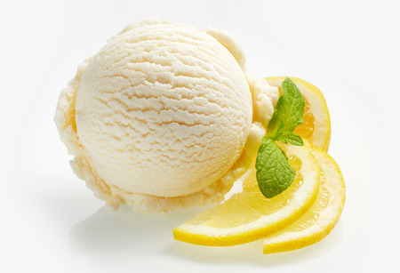 Tangy fresh lemon citrus sorbet or ice cream with sliced fresh fruit garnished with mint alongside over a white background Foto de archivo