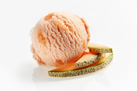 Speciality Italian sweet melon or spanspek ice-cream with slices of fresh fruit alongside over white for use in a menu or advertising