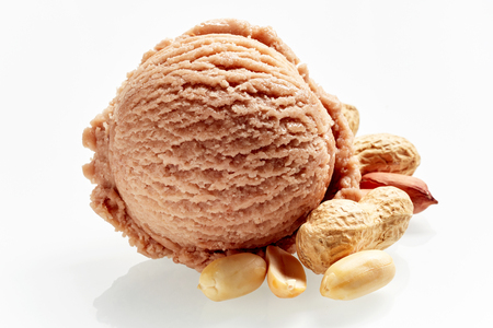 Scoop of artisanal peanut or groundnut Italian ice cream with fresh shelled and whole nuts as ingredients alongside over white for advertising Stock Photo