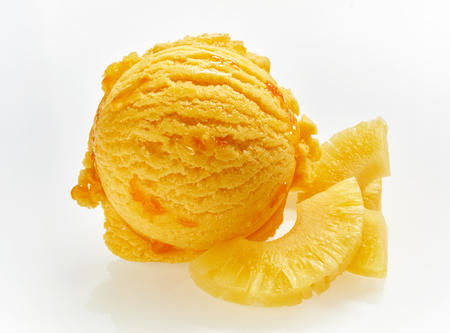 Colorful orange scoop of Italian pineapple ice cream with slices of fresh fruit alongside over white for advertising and use in a restaurant menu