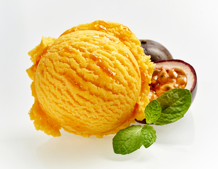 Gourmet scoop of colorful orange granadilla ice cream with a fresh halved fruit showing the pulp behind and sprig of fresh peppermint over white for advertising or a menu Banco de Imagens