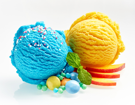 Blauwe en gele roomijslepels met suikergoed, munt en appelplakjesclose-up dat op witte achtergrond wordt geïsoleerd