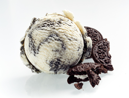 Speciality American oreo ice cream with crushed cookies alongside as ingredients isolated on white showing the texture of the scoop