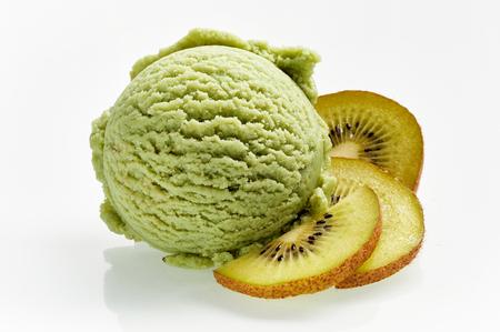 キウイ味と白い背景に分離されたセクションのクローズ アップでキウイ フルーツのスライスとグリーン アイス クリーム スクープ