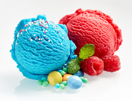 fruit candy: Scoops of gourmet bubblegum and raspberry Italian artisanal ice-cream with sugar coated candy and fresh fruit ingredients alongside over white for use in advertising Stock Photo