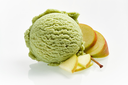 Fresh apple speciality Italian ice cream with sliced fruit alongside on white for use in advertising or a menu Stock Photo