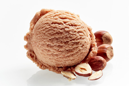 Scoop of delicious creamy hazelnut ice-cream with fresh shelled and whole nuts alongside isolated on white with reflection Фото со стока