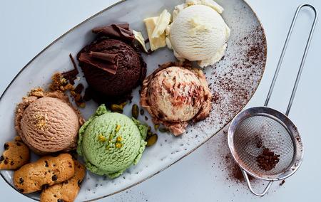 さまざまなおいしいとふるいと白い背景の上の大皿に肴にグルメの味のアイスクリームのスクープの静物ハイアングル 写真素材