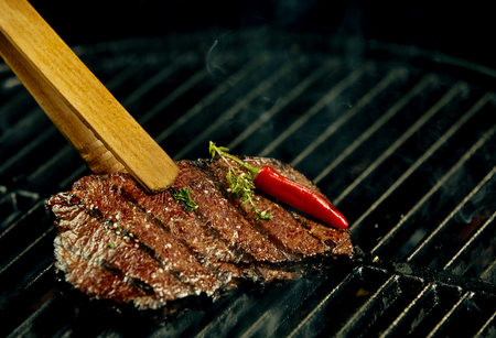 Portion of hot spicy beef steak grilling on a BBQ garnished with a whole red cayenne chili pepper and fresh rosemary in a close up view with copy space