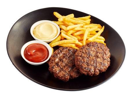 Grilled minced meat stakes and french-fries, served with sauce on black dish isolated on white background Stock Photo