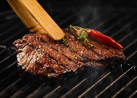 Spicy portion of seared steak grilling on a BBQ seasoned with fresh rosemary and a hot red chili pepper pod being lifted in a pair of wooden tongs