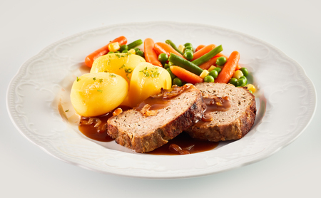 Close Up Still Life of Hearty Dinner Meal - Slices of Meatloaf with Brown Gravy, Roasted Potatoes, and Mixed Vegetables Served in White Dish on White Background