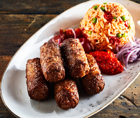 Cevapcici minced beef rolls with vegetables, a popular Eastern European dish, served on an oval plate in a close up high angle view