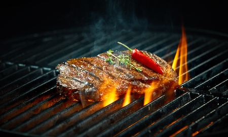 Hot spicy chili steak grilling on a summer barbecue over the flaming hot coals garnished with a whole red cayenne pepper and fresh rosemary Stock Photo