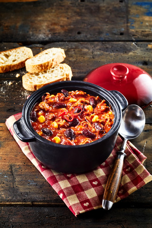 Chili con carne stew and spoon served with white bread on napkin, close-up image on rustic rough wooden table background