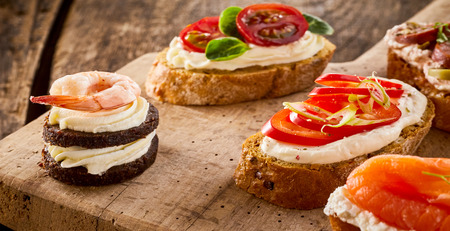 double oven: Assorted fresh seafood and vegetable canapes on bread and blinis with smoked salmon, prawns, tomato and basil served on an old rustic wooden board for appetizers Stock Photo