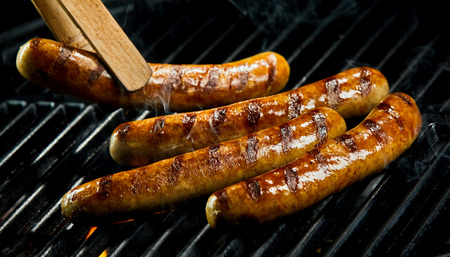 Close-up of wooden tongs turning sausages roasted on barbecue grill