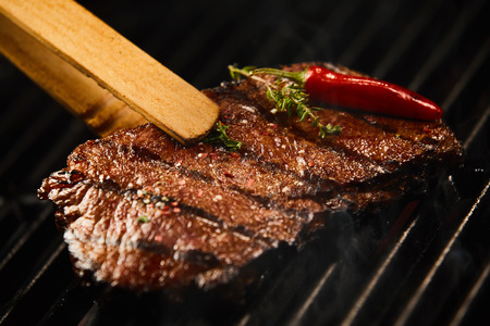 Tasty lean rump steak sizzling on a BBQ fire seasoned with a whole red hot chili pepper and sprig of fresh rosemary in a close up view being lifted off the grill with tongs