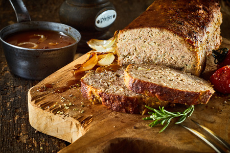 Minced meat loaf on rustic wooden cutting board with spices, close-up image 版權商用圖片