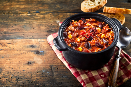 Chili con carne stew served in black iron pan with spoon over red napkin and white bread, on rustic wooden table, close-up image with copy space