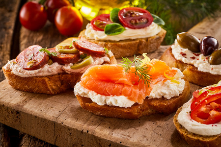 Delicious fresh smoked salmon canape on toasted baguette on a wooden board with assorted varieties of other toppings in a close up view