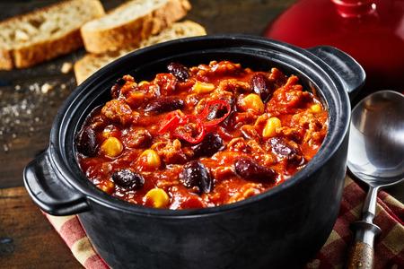 唐辛子詐欺 carne そして素朴なテーブル スプーンの豆シチューの黒鍋のクローズ アップ