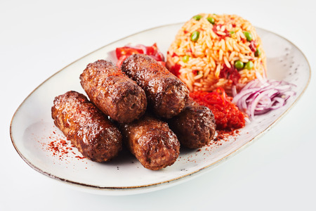 Fried cevapcici grond meat patties seasoned with paprika and served with savory rice and chopped fresh onion on an oval plate Stock Photo