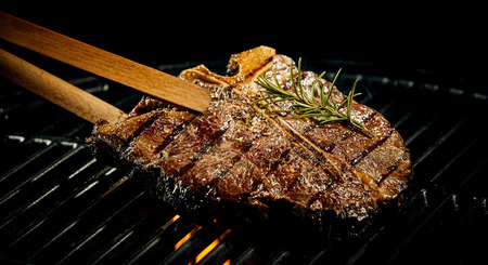 potherb: Marinated spicy lean t-bone steak grilling on a BBQ flavored with a sprig of fresh rosemary being lifted off the fire with a pair of wooden tongs Stock Photo