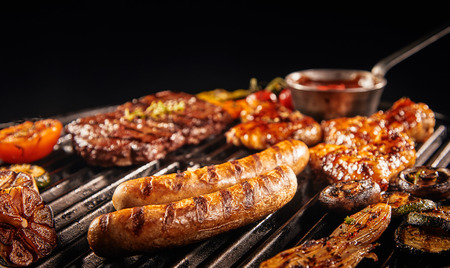 Barbecuing an assortment of meat with pork sausages, beef steak, chicken wings onions, tomatoes and slice garlic bulbs in a low angle close up view