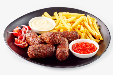Serving of traditional rolled ground meat patties or cevapcici served with French fries and side dishes of ketchup and mayonnaise Stock Photo