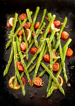 disarray: Delicious roasted green asparagus tips with tomatoes on an old metal oven baking tray viewed from overhead in a decorative pattern for a gourmet starter