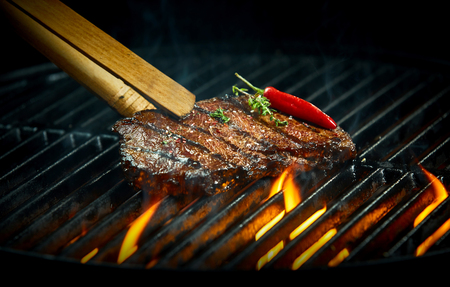 Hot spicy rump steak grilling on a summer barbecue seasoned with fresh rosemary and a red hot chili pepper in a close up view over hot flaming coals