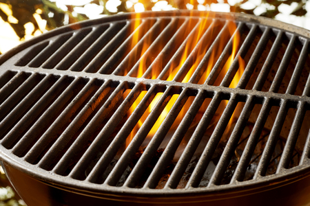 Flaming coals in a portable summer barbecue with the empty grill on top outdoors in the garden with sparkling sunlight bokeh