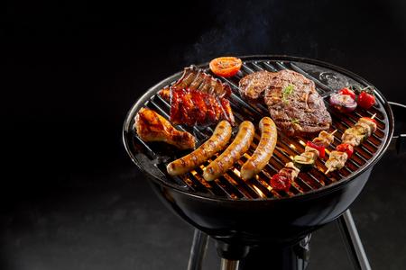 Sortiment von mariniertem Fleisch Grillen über die heißen Kohlen auf einem Grill mit Wurst, Steak, Huhn, Rippchen und Kebabs mit Kopie Raum