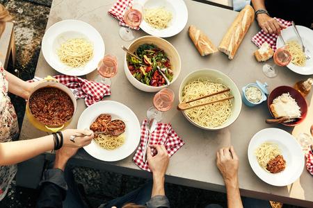 屋外のピクニック テーブルで無愛想なパンとおいしい新鮮なサラダ スパゲッティ ボロネーズの食事、手や食べ物のオーバーヘッドがビューを楽しんでいる友人のグループ 写真素材 - 74249126