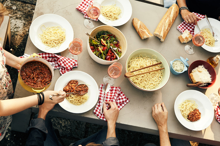 Group of friends enjoying a meal of spaghetti Bolognaise with tasty fresh salad and crusty bread at a picnic table outdoors, overhead view of their hands and the food