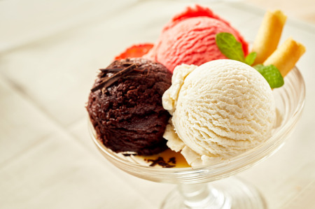 Bowl with ice cream with three different scoops of white, brown and red colors, close-up over white table