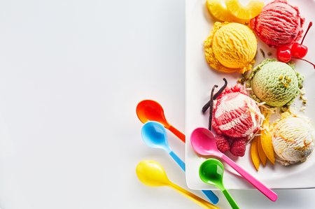 Assortment of Italian ice cream scoops with fresh ingredients on a platter with brightly colored plastic party spoons, overhead view with copy space Stock Photo