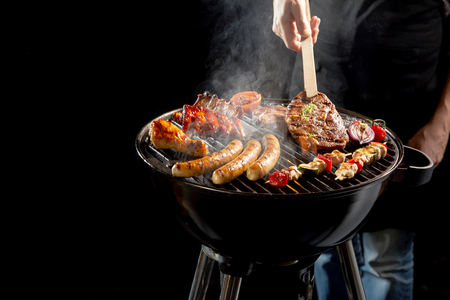 portables: Man grilling an assortment of meat and kebabs on a portable barbecue lifting a t-bone steak with a pair of tongs in a close up view of his hand Stock Photo