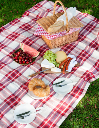 Delicious healthy spread for a summer picnic with croissants, baguette, fresh fruit and cheese arranged on a red and white checkered rug on green grass with a wicker hamper Standard-Bild