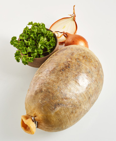neeps: Stuffed savory sheep stomach or haggis, a traditional Scottish dish, filled with the lungs, heart and liver mixed with seasoning, suet, oatmeal and onion over a white background with ingredients